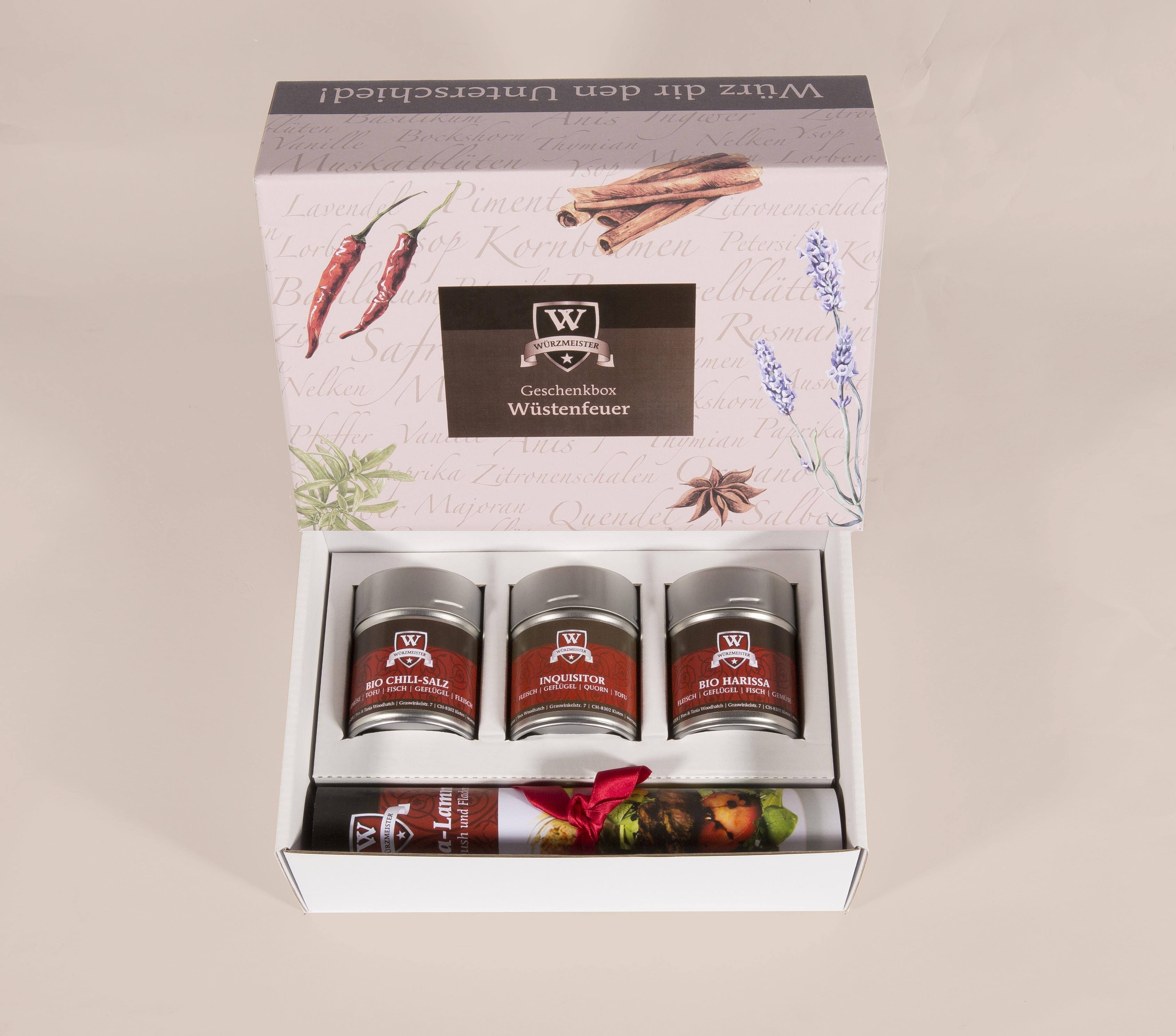 Bild mit der Geschenkbox Wüstenfeuer. Sie beinhaltet 3 Dosen mit den Gewürzmischungen Bio Chili-Salz, Inquisitor und Bio Harissa. Dabei ist ein passendes Rezept.