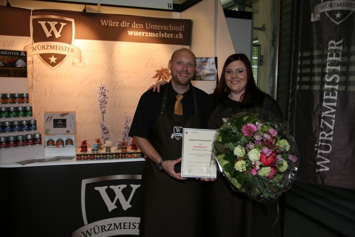 Bild zum Beitrag Würzmeister gewinnt den Jungunternehmerpreis Kloten 2014. Yves und Tania präsentieren den Preis vor dem Stand.